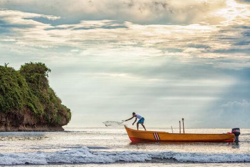 Man casting his fishing net at sunrise in Puerto Viejo, Costa Rica