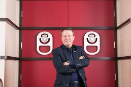 Cott Beverages CEO Jerry Fowden standing in front of large red door at the Cott headquarters in Tampa - Carver Mostardi Photography - Tampa corporate portraits.