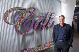 Cott Beverages CEO Jerry Fowden standing next to Cott sign in Tampa headquarters - Carver Mostardi Photography - Tampa corporate portraits.