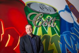 Cott Beverages CEO Jerry Fowden in front of Cott sign and graffiti art work in their Tampa headquarters - Carver Mostardi Photography - Tampa corporate portraits.