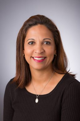 Professional headshot of female executive in a black shirt with light gray background.