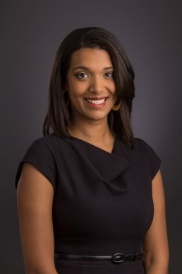Business portrait of a young female executive in a black top with a dark gray background.