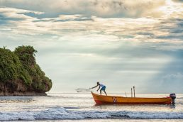 Man casting his fishing net at sunrise in Puerto Viejo, Costa Rica