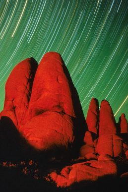 Star trails agains glowing red rocks at Joshua Tree National Park, California.