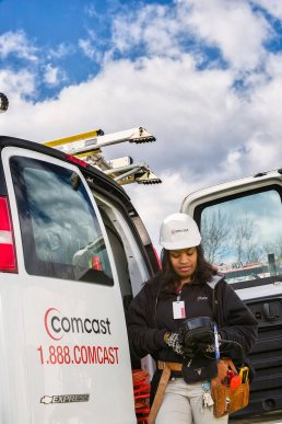 Female Comcast service technician working with handheld device outside of her work van.