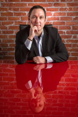 Male executive seated at red table against a brick wall photograph by professional photographer Carver Mostardi.