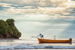 Lone fisherman casts net at sunrise in Puerto Viejo, Costa Rica by Tampa photographer Carver Mostardi.
