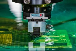 Photograph of CNC machine milling parts in green dielectric fluid by Tampa Industrial photographer Carver Mostardi.