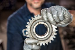 Close-up detail photograph of automotive technician holding transmission gear in auto shop Tampa, Florida.