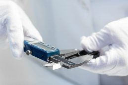 Technician in white lab coat taking measurement with electronic caliper photographed on location by Tampa commercial photographer Carver Mostardi.